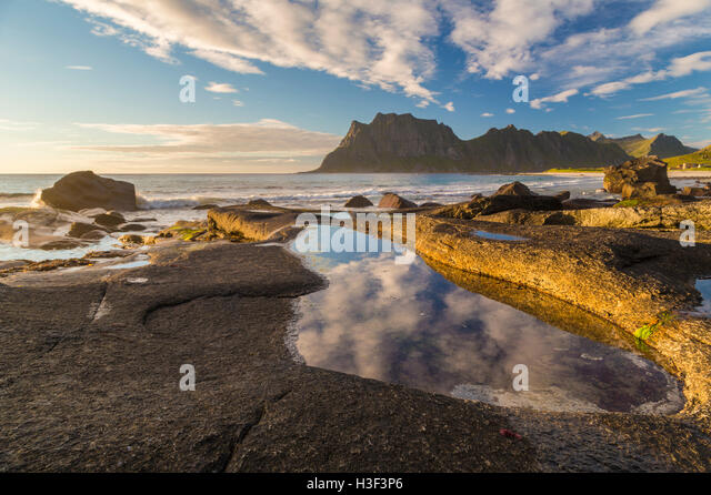Rocks in evening light with warm light shining on them with sky reflecting in a pool of water, high mountains in - Stock Image