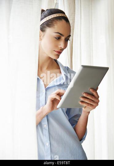 Woman using digital tablet at window - Stock-Bilder