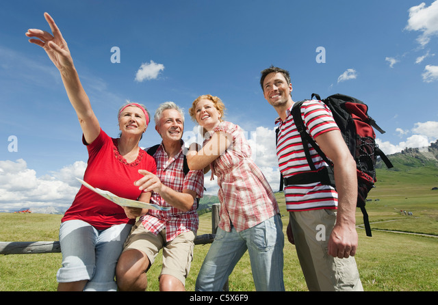 Italy, Seiseralm, Four persons holding map, portrait - Stock Image