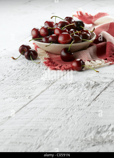 bowl of cherries on rustic white table - Stock Image