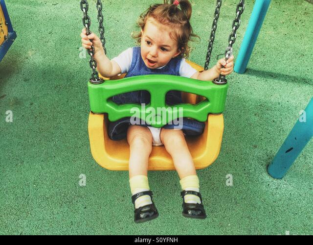Baby girl on the swing - Stock Image
