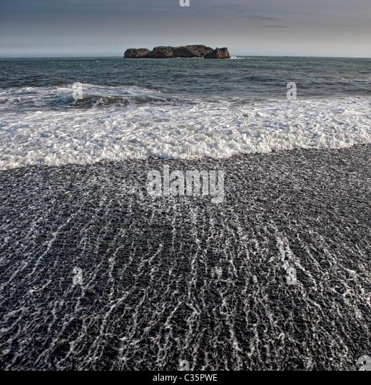 Black sand beach with waves, Dyrholaey, Iceland - Stock Image