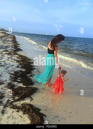 Woman With Her Baby Girl On The Beach - Stock Image
