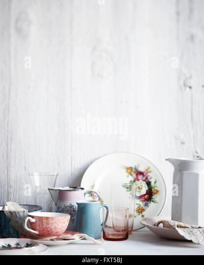 Variety of drinking glasses, plates and jugs on whitewashed table - Stock Image