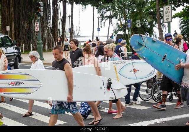 Waikiki Beach Honolulu Hawaii Hawaiian Oahu Kalakaua Avenue pedestrian crosswalk surfer surfers surfboard surfboards - Stock Image