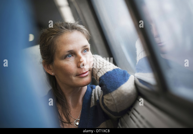 A woman sitting at a window seat in a train carriage resting her head on her hand Looking into the distance - Stock-Bilder