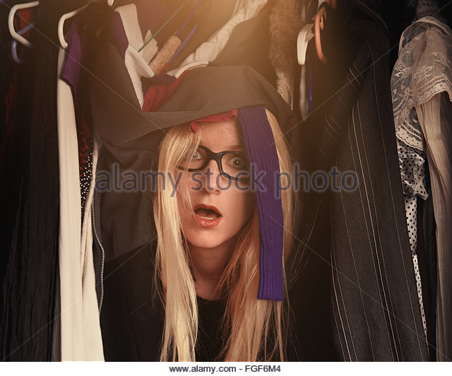 A woman is overwhelmed in a closet of messy clothes with glasses for a style or fashion concept. - Stock Image