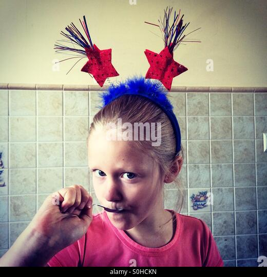 Pretty young girl with patriotic headband eating - Stock-Bilder