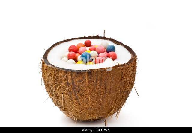 Halved coconut with colorful assortment balls isolated on white - Stock Image