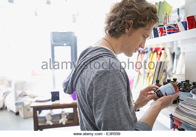 Man looking at bottle label in shop - Stock Image