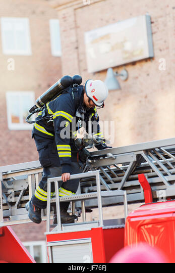 Firefighter standing on top of firetruck - Stock Image