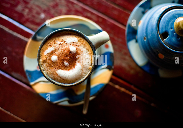 Close up photo of a cup of espresso with a smiling face made of foam. - Stock-Bilder