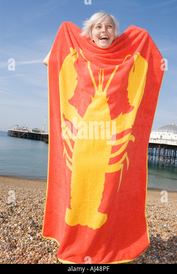 young woman at the beach holding up a red beach towel which a yellow lobster printed on it - Stock-Bilder