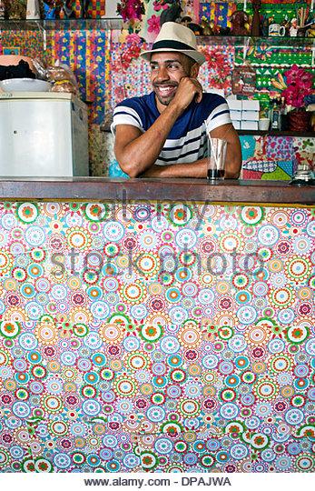 Man at counter of cafe bar - Stock Image