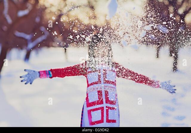 Girl (8-9) throwing snow - Stock Image
