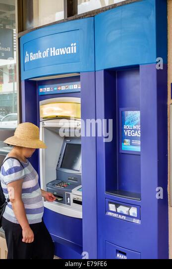 Hawaii Hawaiian Oahu Honolulu Chinatown Bank of Hawaii ATM self-service Asian woman using banking - Stock Image