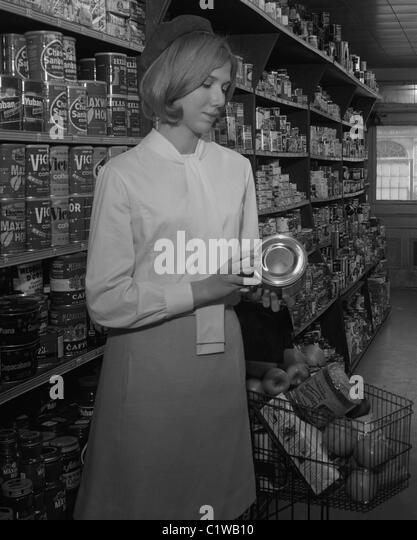 Woman reading labels in supermarket - Stock Image
