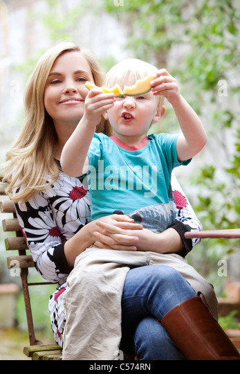 Mother holding son with slice of melon - Stock Image