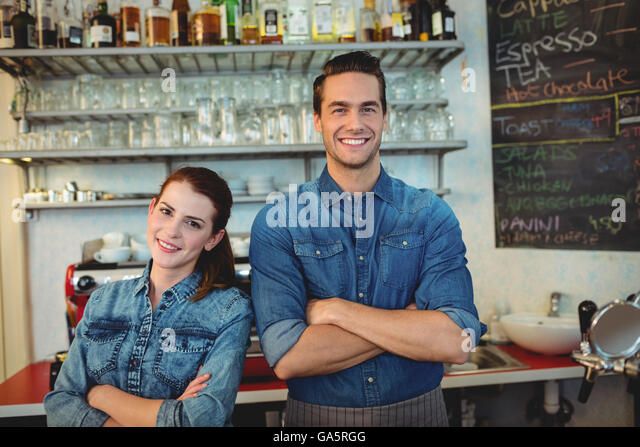 Portrait of happy co-workers at cafeteria - Stock Image