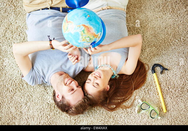 Restful couple with globe lying on the floor and dreaming of summer vacations - Stock Image