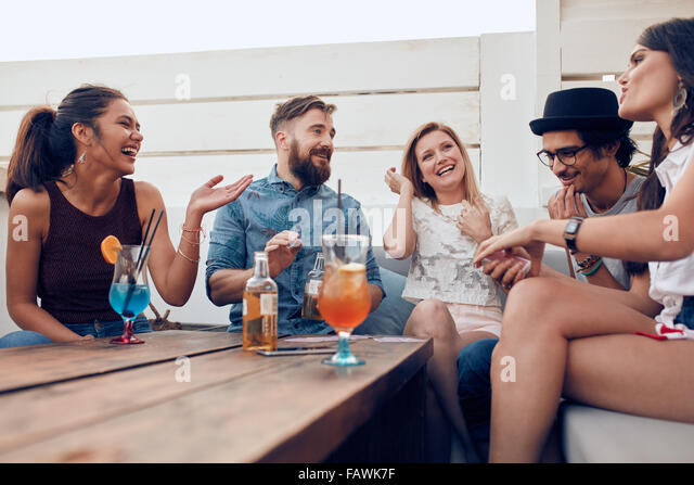 Portrait of happy young people sitting together and laughing. Multiracial friends enjoying at a party with cocktails - Stock Image