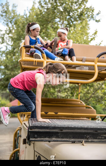 Girl climbs onto safari truck with friends - Stock Image
