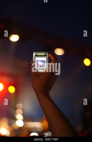 A hand holding up mobile phone at festival - Stock Image
