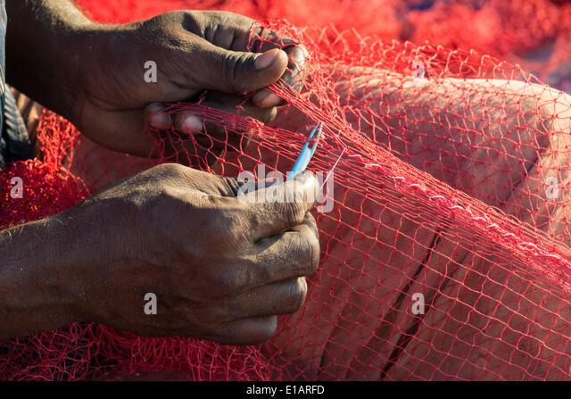 The hands of a fisherman repairing fishing nets, Varkala, Kerala, India - Stock-Bilder