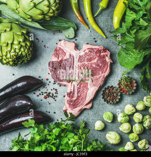Raw beef t-bone steak with vegetables and spices, square crop - Stock Image
