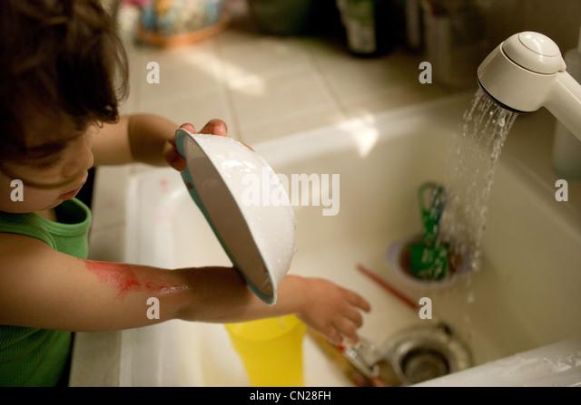 Toddler girl washing up - Stock-Bilder