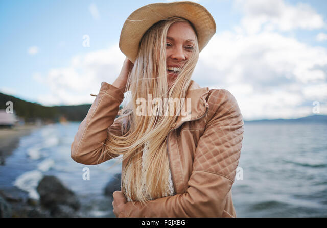 Young woman in hat and leather jacket spending leisure by the seaside - Stock Image