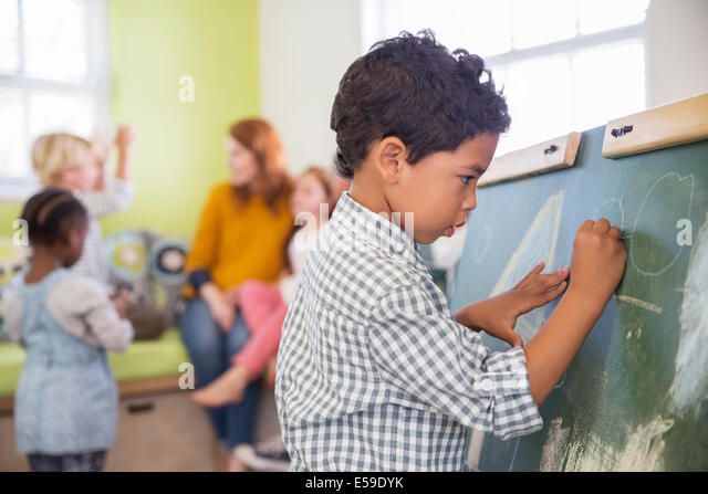 Student drawing on chalkboard in classroom - Stock Image