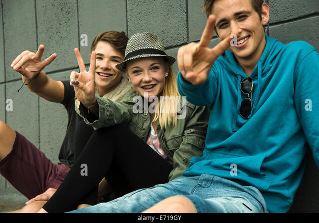 Three teenage friends making peace hand sign - Stock-Bilder