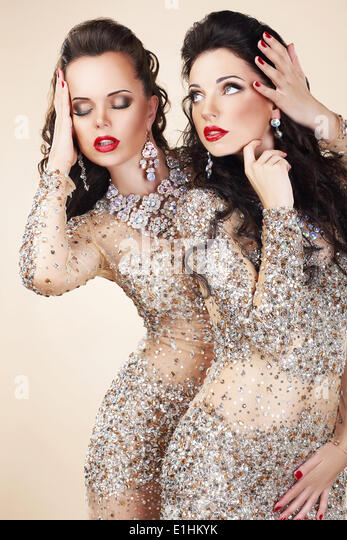 Two Glamorous Women in Evening Dresses and Jewelry Dancing - Stock Image