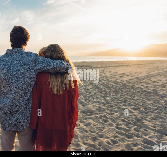 Young couple standing on beach, hugging, rear view - Stock-Bilder
