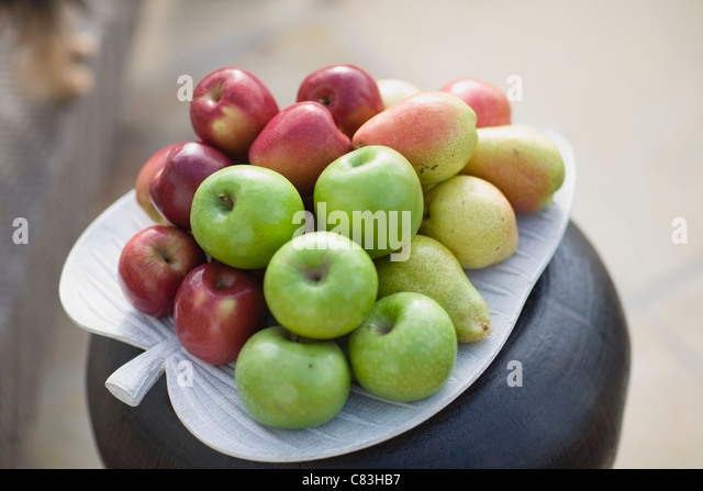 Pile of fruit on plate - Stock Image