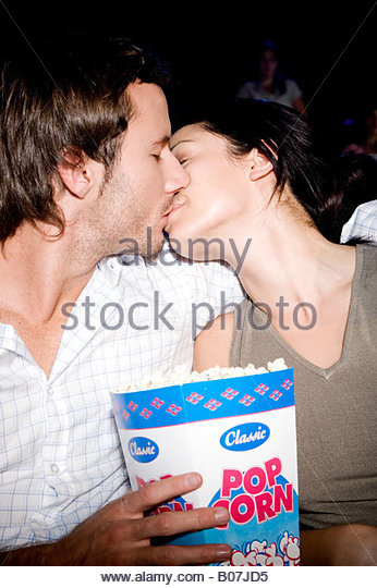 A couple kissing in a cinema - Stock Image
