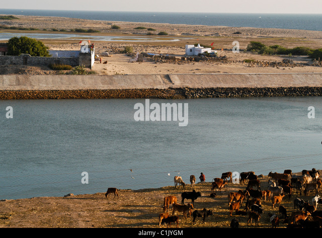 River Gomti with ancient shrines on banks meets Indian Ocean where original golden city Dwarka of Lord Krishna was - Stock Image