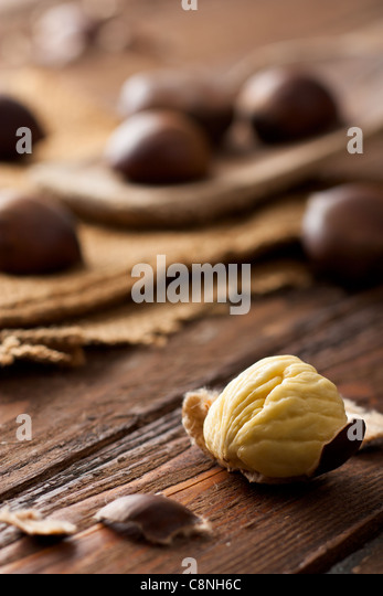 Raw Chestnuts on Wood with Jute and Wooden Spoon - Stock Image