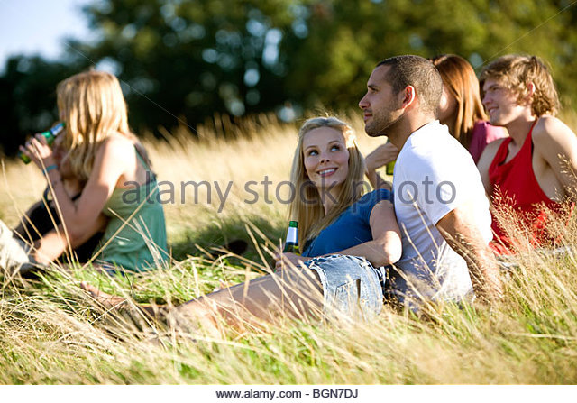 A group of young people sitting in a park, drinking beers - Stock Image