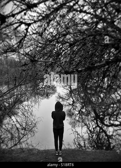 A person wearing a hoodie looking out at water surrounded by trees. - Stock Image