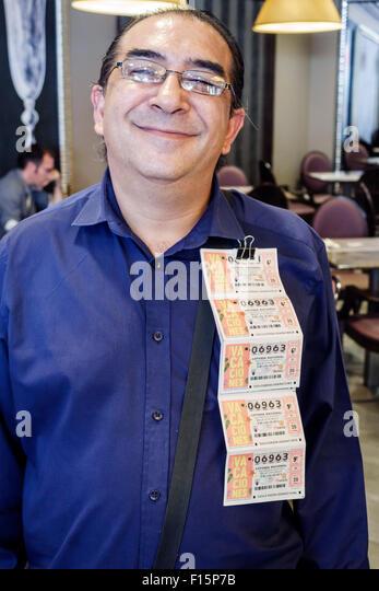 Spain Europe Spanish Madrid Retiro lottery ticket salesman vendor Hispanic man selling - Stock Image
