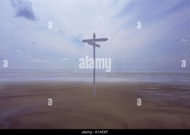 Sign post on vast empty beach - Stock Image