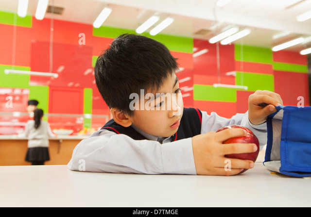 School boy checking lunch bag in school cafeteria - Stock Image