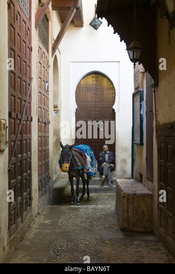 Man sat resting while his donkey eats from a home-made nosebag. Backed by lovely traditional-shaped doorway and - Stock Image
