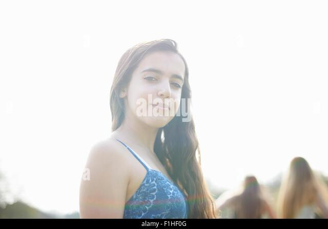 Portrait of pretty long haired teenage girl in park - Stock Image