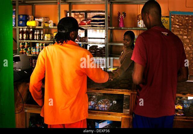 Prisoner, orange dressed, handling in a shop, at D´Kar Ghanzi Farms, Botswana - Stock Image