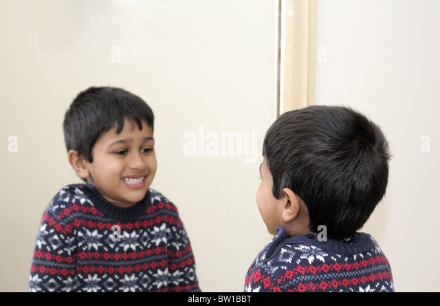 Cute toddler looking into mirror, laughing - Stock Image