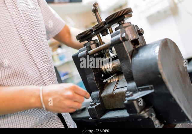 Goldsmith using machine to make metal thinner - Stock Image