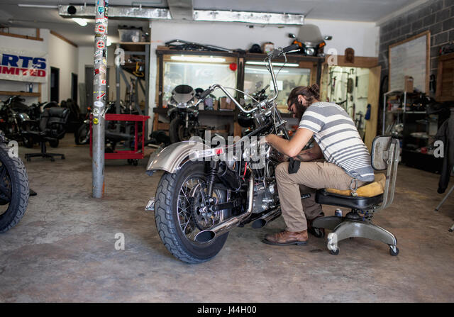 Young man repairing a motorcycle - Stock Image